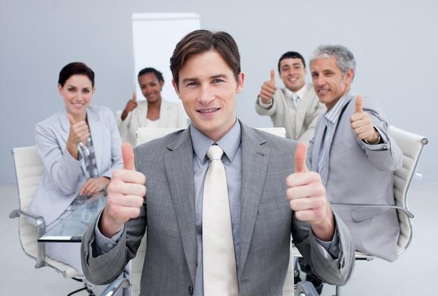 Homem de negócios atraente que comemora um sucesso com seu time