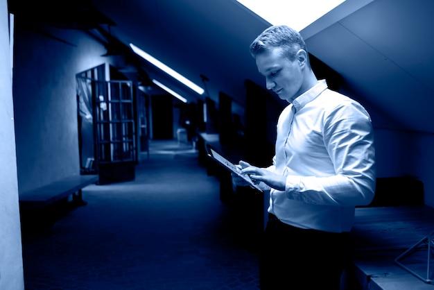 Homem de negócios atraente usando tablet digital no escritório, cor da tendência do ano 2020, tom clássico de azul