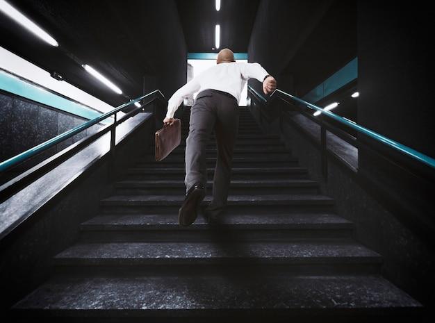 Homem de negócios atrasado com bolsa corre nas escadas