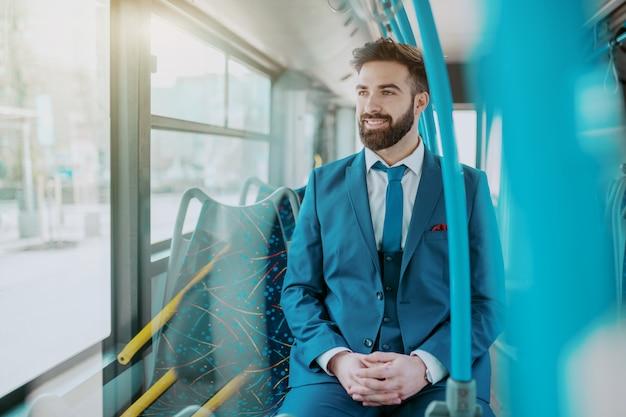 Homem de negócios atrativo de sorriso dos jovens no terno azul que senta em ônibus público e que olha a janela da calha.