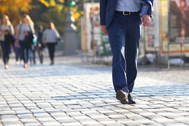 Homem de negócios atravessando a rua em uma travessia de pedestres na calçada