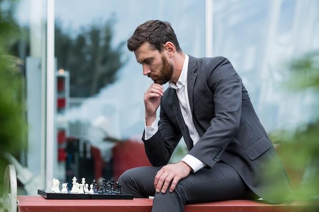 Homem de negócios banqueiro jogando xadrez, sentado no banco perto do escritório, pensativo, fazendo um movimento estratégico