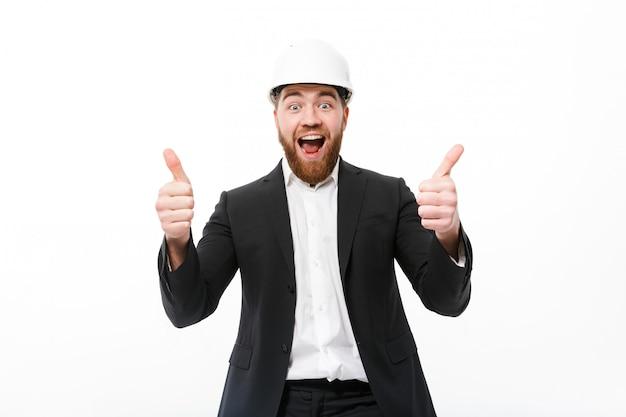 Homem de negócios barbudo alegre no capacete protetor mostrando os polegares