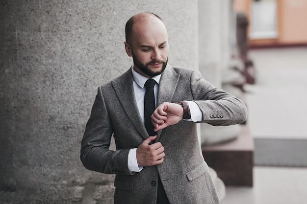 Homem de negócios barbudo bonito em terno clássico olhando para o relógio na cidade