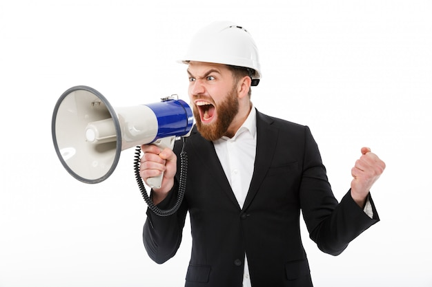 Homem de negócios barbudo com raiva no capacete protetor, gritando no megafone