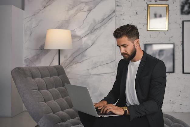 Homem de negócios barbudo elegante sentado no sofá confortável com o computador portátil em seu laptop, digitando carta comercial via e-mail, tendo focado o olhar sério. tecnologia, comunicação e negócios