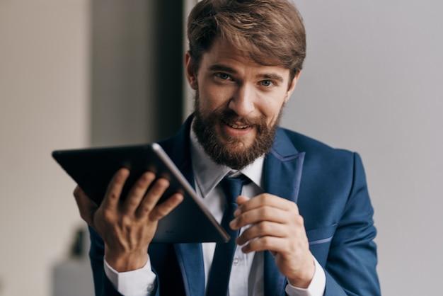 Homem de negócios barbudo em tablet de terno em mãos trabalhando tecnologia