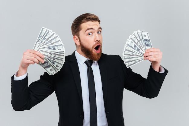 Homem de negócios barbudo feliz em terno preto segurando dinheiro nas mãos