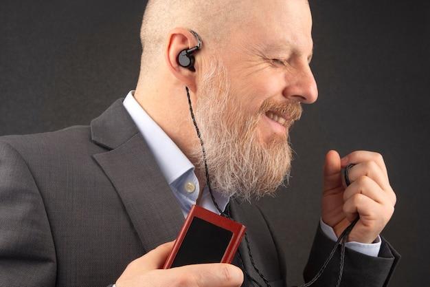 Homem de negócios barbudo gosta de ouvir sua música favorita em casa com um reprodutor de áudio em pequenos fones de ouvido. música e som hi-fi.