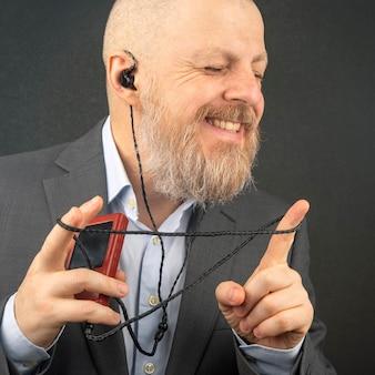 Homem de negócios barbudo gosta de ouvir sua música favorita em um reprodutor de áudio com pequenos fones de ouvido. audiófilo e amante da música. música e som hi-fi