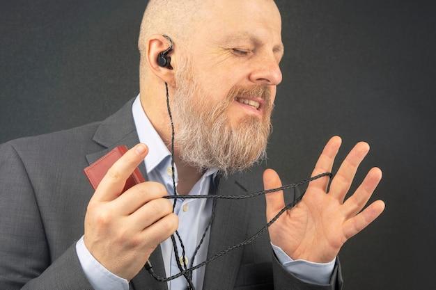 Homem de negócios barbudo gosta de ouvir sua música favorita por meio de um reprodutor de áudio em pequenos fones de ouvido.