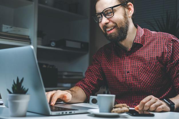 Homem de negócios barbudo jovem e atraente, vestido de maneira casual, trabalhando no escritório, sentado na mesa branca, usando um laptop
