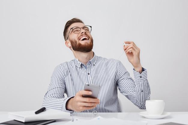Homem de negócios barbudo não para de rir enquanto ouve anedotas ou piadas com fones de ouvido