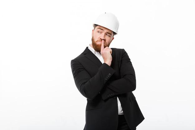 Homem de negócios barbudo pensativo no capacete protetor, olhando para longe