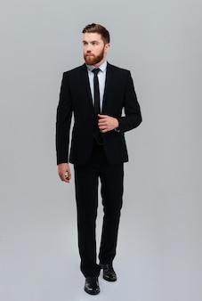 Homem de negócios barbudo segurando um terno no estúdio e olhando para o lado. fundo cinza isolado
