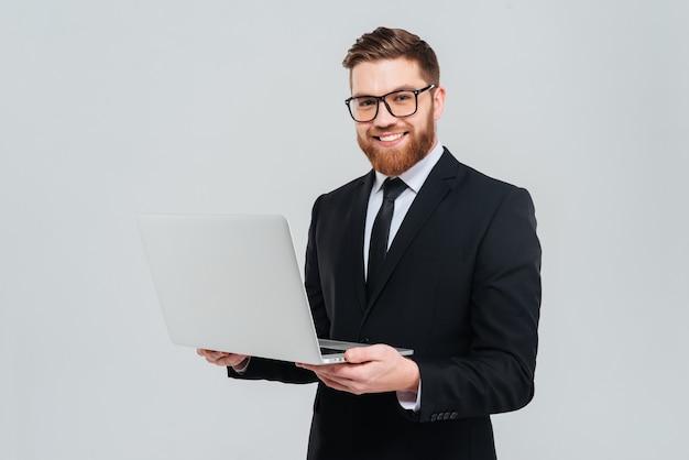 Homem de negócios barbudo sorridente de óculos e terno preto segurando um laptop