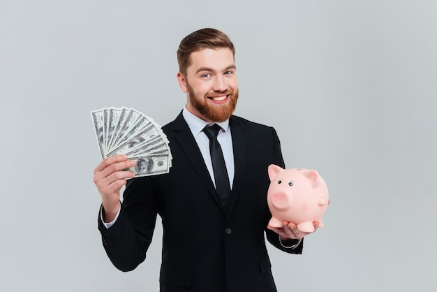 Homem de negócios barbudo sorridente de terno com dinheiro e caixa de dinheiro