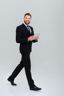 Homem de negócios barbudo sorridente de terno se move com computador tablet
