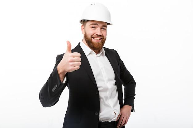 Homem de negócios barbudo sorridente no capacete protetor aparecendo polegar