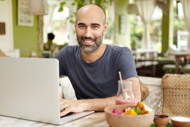 Homem de negócios barbudo vestido de maneira casual, verificando e-mails em seu laptop durante o café da manhã, sentado em um bom café, bebendo smoothie com uma expressão de rosto feliz e confiante, aproveitando as férias