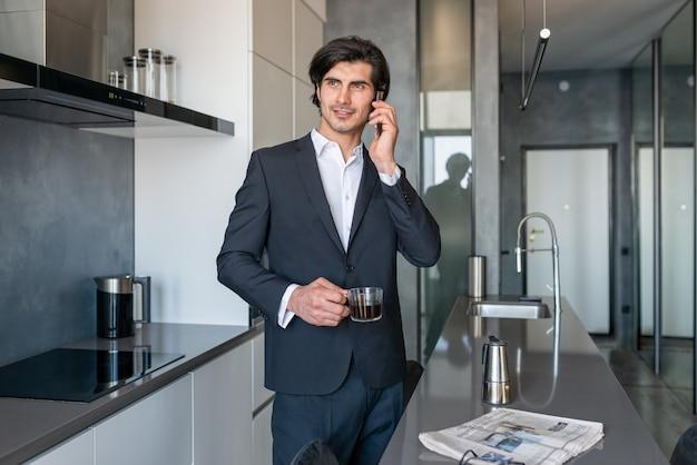 Homem de negócios bebe uma xícara de café na casa dela, enquanto lê notícias do jornal