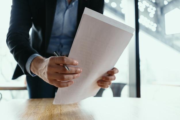 Homem de negócios bem sucedido, assinar documentos em um escritório moderno