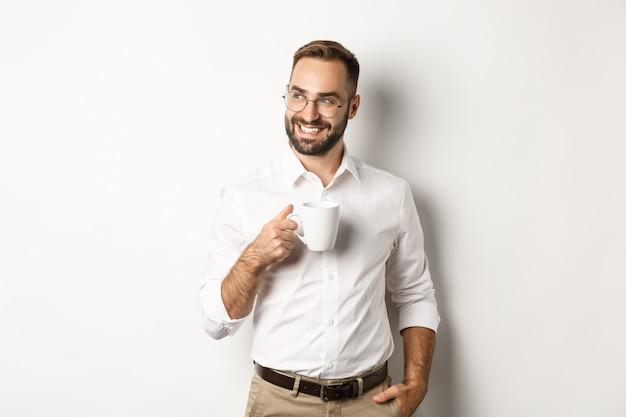 Homem de negócios bem-sucedido, bebendo café, olhando de soslaio com um sorriso satisfeito, em pé sobre um fundo branco.