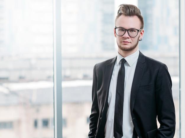 Homem de negócios bem-sucedido com atitude ambiciosa. retrato de jovem líder confiante em um escritório moderno.