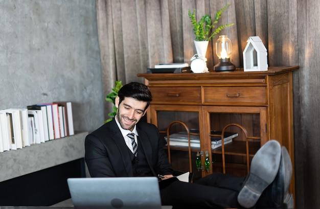 Homem de negócios bem-sucedido em relaxar ou dormir depois de terminar o trabalho colocou os pés na mesa