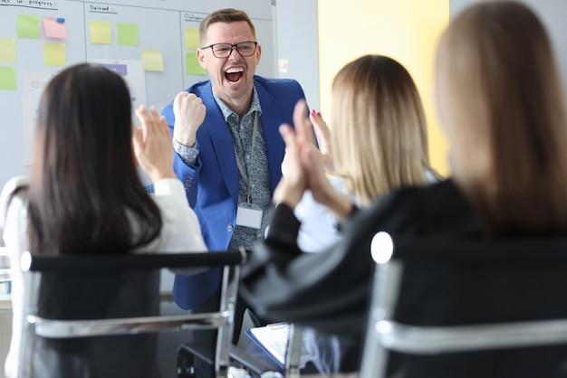 Homem de negócios bem-sucedido falando na conferência, pessoas aplaudindo na platéia