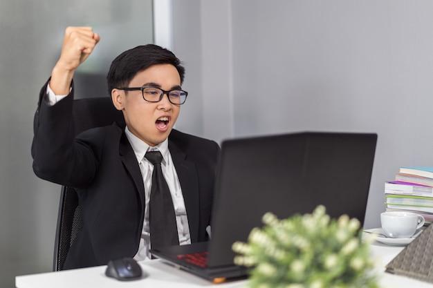 Homem de negócios bem sucedido feliz usando o computador portátil