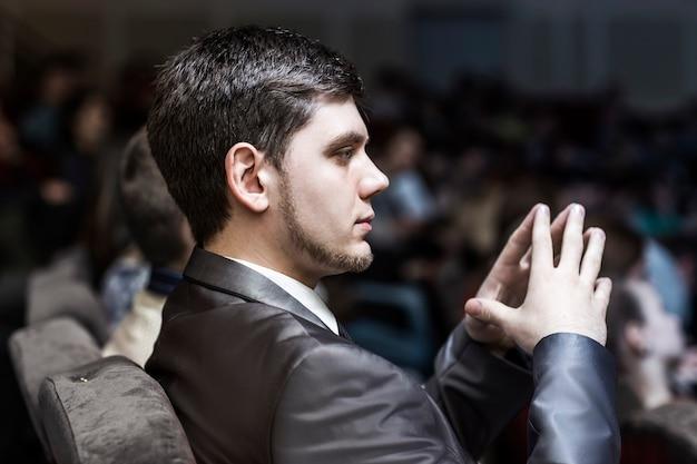 Homem de negócios bem-sucedido ouve a reportagem sentado na sala de conferências