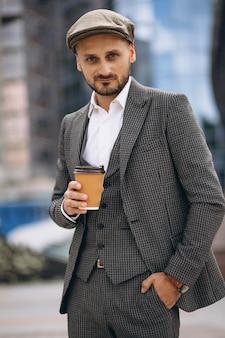 Homem de negócios bem sucedido pelo arranha-céu bebendo café