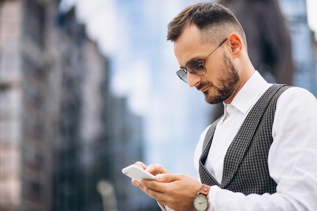 Homem de negócios bem sucedido pelo arranha-céu, falando ao telefone Foto gratuita