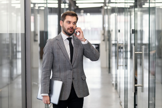Homem de negócios bem sucedido tem conversa telefônica em pé no corredor do escritório vazio. banqueiro profissional masculino em terno falando no celular durante as férias de trabalho.