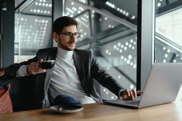 Homem de negócios bem sucedido trabalhando no laptop enquanto bebia café