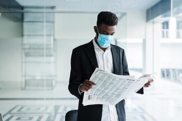 Homem de negócios bonito africano na máscara médica, lendo o jornal no prédio de escritórios