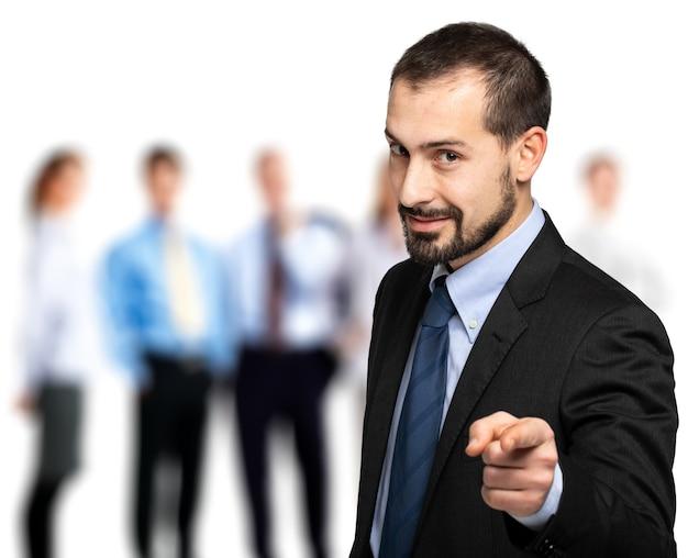 Homem de negócios bonito apontando o dedo para você na frente de sua equipe