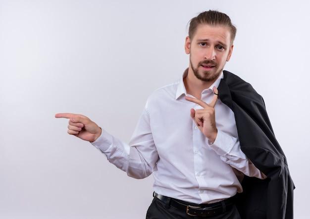Homem de negócios bonito carregando sua jaqueta no ombro olhando para a câmera sorrindo confiante apontando com figos ao lado em pé sobre um fundo branco