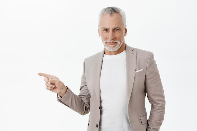 Homem de negócios bonito com cabelo grisalho apontando o dedo para a esquerda