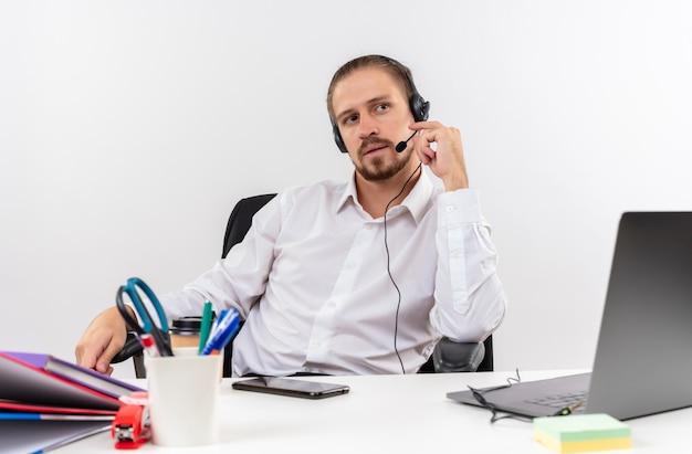Homem de negócios bonito com camisa branca e fones de ouvido com microfone olhando para o lado com cara séria sentado à mesa em escritório sobre fundo branco
