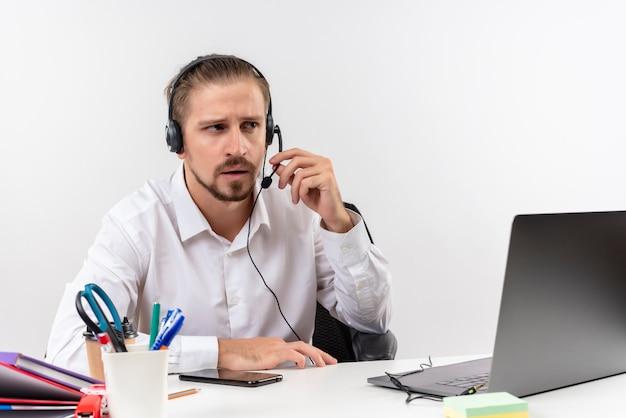Homem de negócios bonito com camisa branca e fones de ouvido com microfone ouvindo um cliente com cara séria sentado à mesa em escritório sobre fundo branco