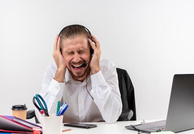 Homem de negócios bonito com camisa branca e fones de ouvido com um microfone gritando com expressão irritada com os olhos fechados sentado à mesa em escritório sobre fundo branco