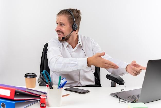 Homem de negócios bonito com camisa branca e fones de ouvido com um microfone trabalhando em um laptop, olhando de lado confuso, sentado à mesa em escritório sobre fundo branco