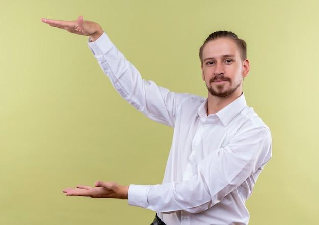 Homem de negócios bonito com camisa branca mostrando uma placa de tamanho grande parecendo confiante, símbolo de medida em pé sobre fundo verde-oliva