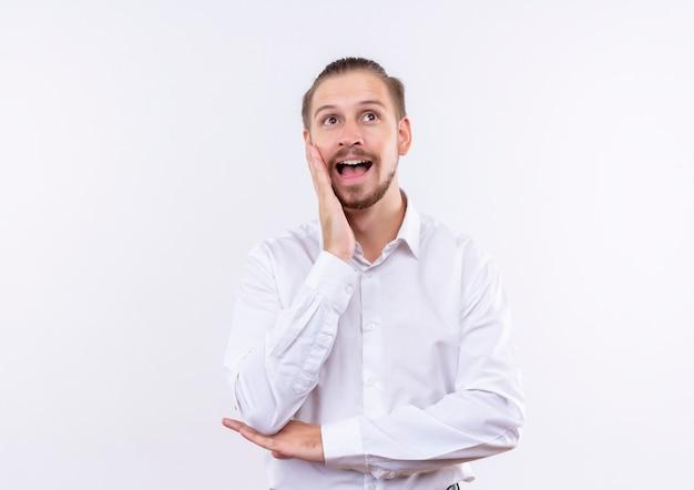 Homem de negócios bonito com camisa branca olhando de lado surpreso e surpreso em pé sobre um fundo branco