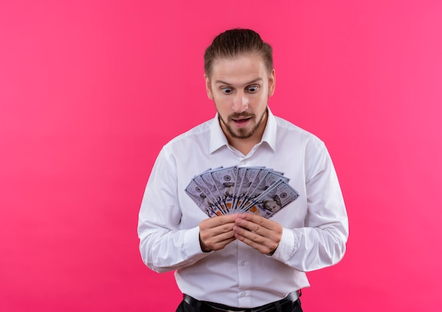 Homem de negócios bonito com camisa branca segurando dinheiro parecendo espantado e surpreso em pé sobre um fundo rosa