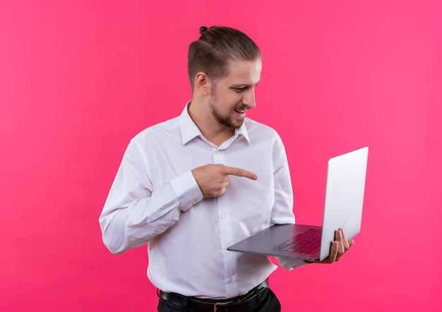 Homem de negócios bonito com camisa branca segurando laptop apontando com o dedo para a tela do laptop confuso em pé sobre um fundo rosa