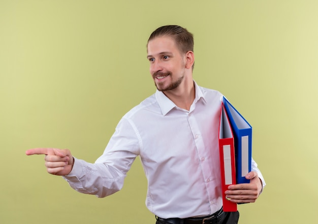 Homem de negócios bonito com camisa branca segurando pastas olhando para o lado apontando com o dedo indicador para o lado sorrindo em pé sobre fundo verde-oliva
