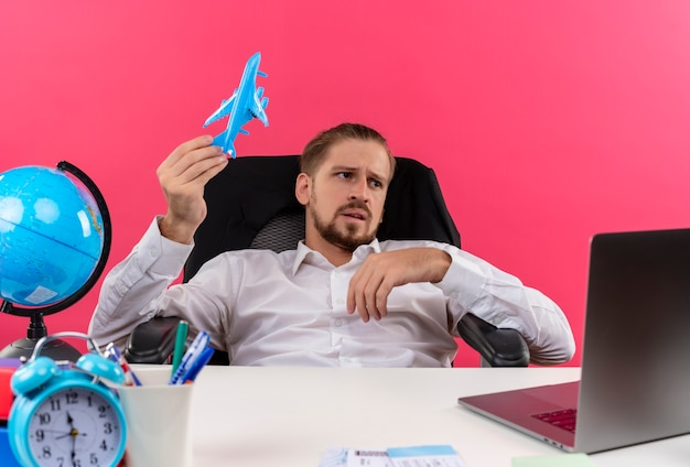 Homem de negócios bonito com camisa branca segurando um avião de brinquedo olhando de lado perplexo, sentado à mesa em escritório sobre fundo rosa